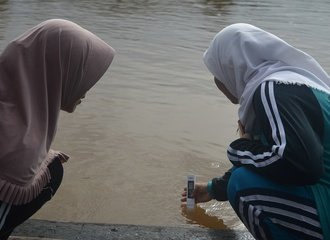 4 - Two members of the Semanga women's group test the level of heavy metals in the surface flow of the Sambas River