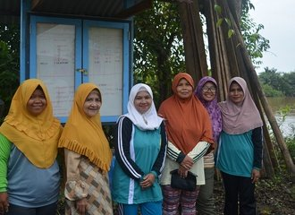 7 - Members of the Kampai women's group in front of the community notice board where they record their test results