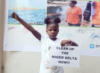 "Girl with sign saying ""Clean up the Niger Delta now"""