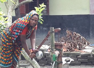 woman at the water pump in Hogladanga, Bangladesh