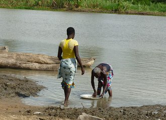 women wash dishes in the river near Cotonou, Benin